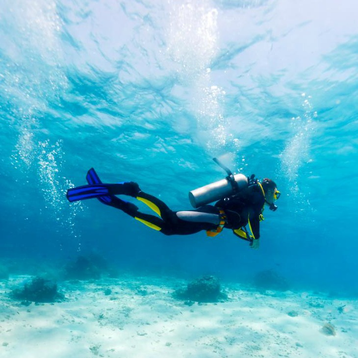 uscuba-diver-swimming-underwater-above-white-sand